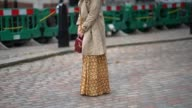 A guest wears sunglasses a camel trench coat a gold dress a red bag outside Preen by Thornton Bregazzi during London Fashion Week September 2017 on...