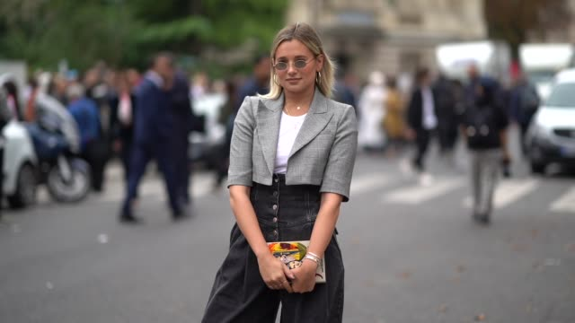 A guest wears sunglasses a white top a grey Prince of Wales checked bolero jacket black denim pleated and highwaisted pants a gold colour bag outside...