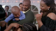 Guests cheering up crying toddler held by father at wedding reception / Arizona