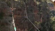 Guilherme Lopes of Brazil walks on a 60m highline and Joseph Huard of Canada walks on a 90m highline rigged between cliffs at Corroboree Walls in...
