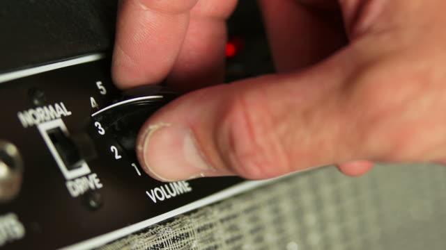 Guitar Player Turning Amplifier Volume Knob