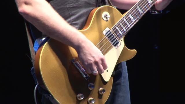 Guitarist plays Electric guitar at live concert / gig