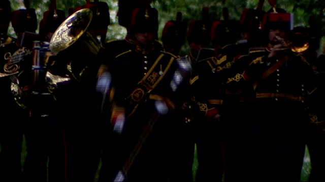 **Music heard SOT** Military bands marching towards