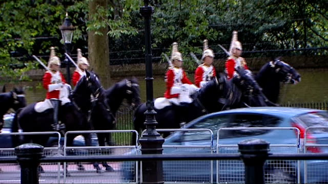 Gun Salute in Green Park Mounted police officers along road past traffic/ Mounted cavalry riding along road on horse back / people along in park /...