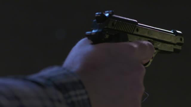 CU of gunman shooting handgun at woman
