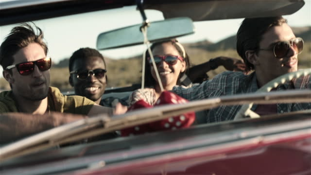 Guy air-drums to the radio in backseat of classic convertible