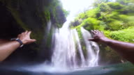 Guy during travel vacations enjoy swim under the stunning waterfalls with wild nature in Indonesia from personal perspective using action cam.