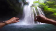 Guy during travel vacations enjoy swim under the stunning waterfalls with wild nature in Indonesia from personal perspective.