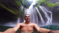 Guy during travel vacations enjoy swim under the stunning waterfalls with wild nature in Indonesia taken video selfie with action cam.