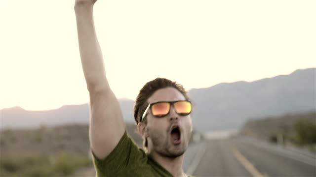 Guy in backseat of convertible stands with his fist in the air and high-fives friends