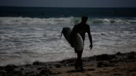 Guy walking on beach with surf board