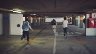 Guys running in parking garage