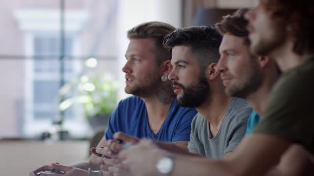 Jungs sitzen auf der couch spielen Videospiele und jubeln
