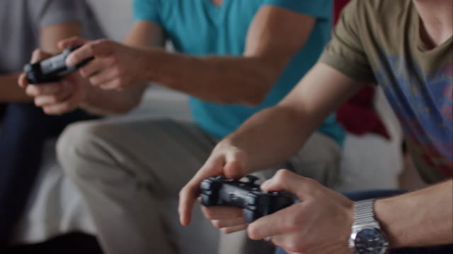 Guys sitting on couch playing video games