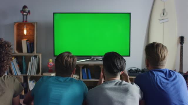 Amici seduto sul divano guardando la televisione e tifo