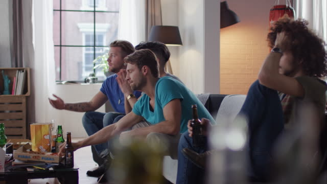 Guys sitting on couch watching tv disappointed