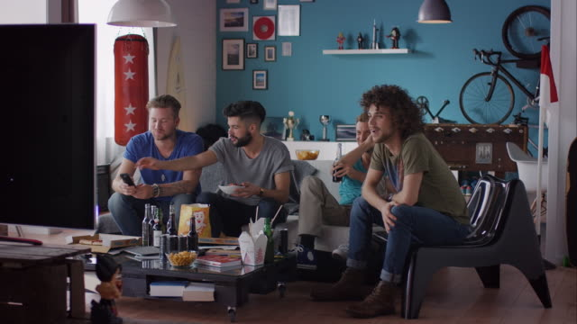 Guys sitting on couch watching tv