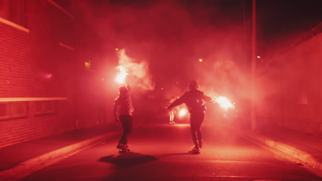 Guys skateboarding with torches on a street