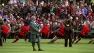 Aberdeenshire Braemar EXT Girls dancing on stage in tartan skirts and socks / Tug of war event / Running race event / Tug of war event GVs / Men...