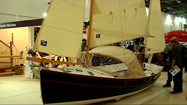 GVs exhibits at London Boat Show Hambleden classic boat stand with wooden long boat on display Wooden yacht on display Man in sailor's uniform...