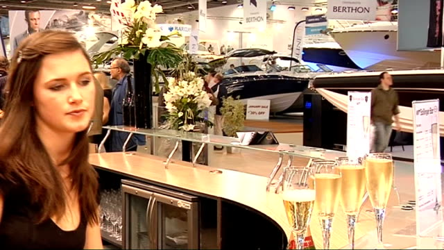GVs exhibits at London Boat Show INT SIDE shot of line of yacht hulls on display Close Shot of glasses of champagne PULL OUT as another glass poured...