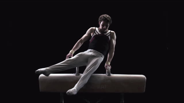 SLO MO Gymnast mounts and performs on a pommel horse then dismounts / Auckland, New Zealand