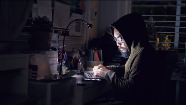 Hacker in hood cracking code using laptop and computers from his dark hacker room