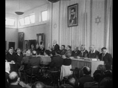 Haganah soldiers stand outside Tel Aviv building / montage Jewish provisional government members sit at table in hall of Tel Aviv Museum as leader...