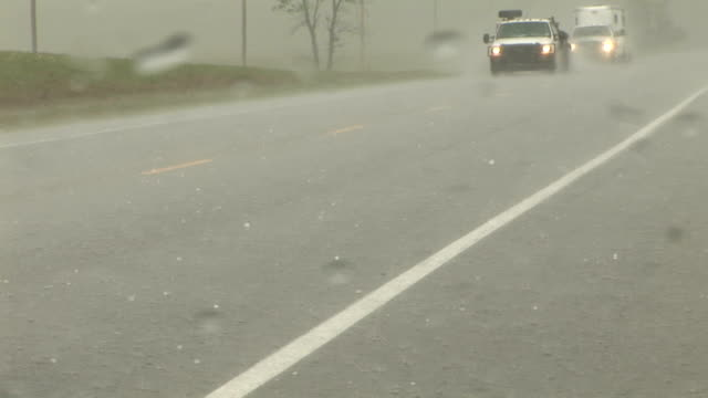 Hail stones fall on a road near Wakita OK as seen through the windshield of a storm chasers vehicle