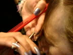A hairdresser cuts the fringe of a customer in a salon 2000