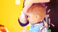 Hairdresser cutting cute childs hair