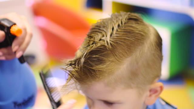 Hairdresser cutting cute childs hair