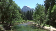 Half Dome Peak looms above a gently flowing river in Yosemite National Park.