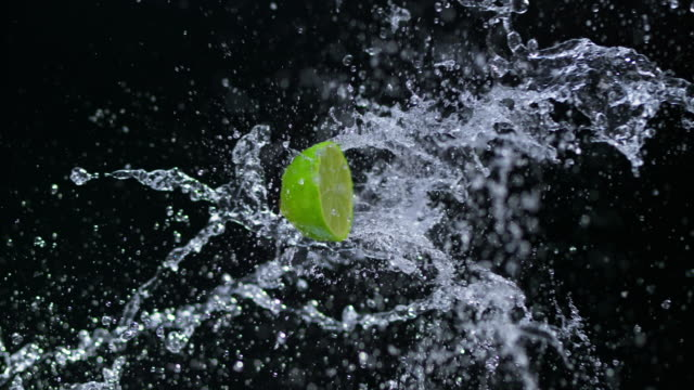 SLO MO Half of lime hitting a water splash in the air