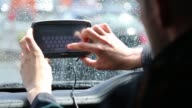 A Halford employee adjusts a TomTom navigation system manufactured by TomTom NV as it sits on a vehicle windscreen in Manchester UK on Friday May 29...