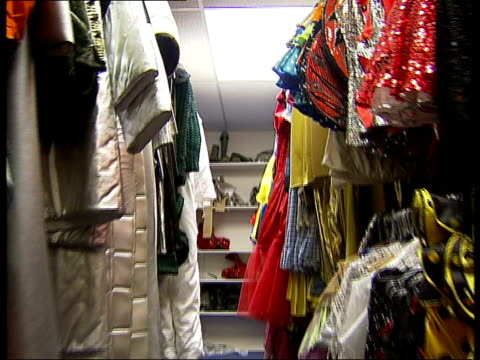 London costumier 'Angels' interiors with Halloween and other Fancy Dress costumes Red shiny platform shoes PULL OUT to other shoes on shelf tracking...