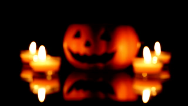 Halloween pumpkin scary face with candle on black background