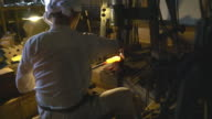 Hammer beating glowing metal bar into shape
