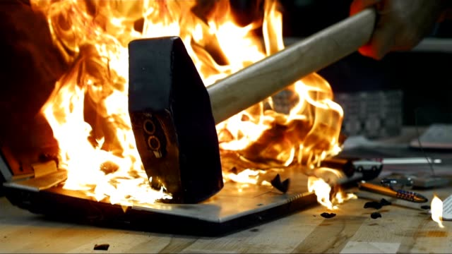 SLO MO LD Hammer hitting a burning laptop