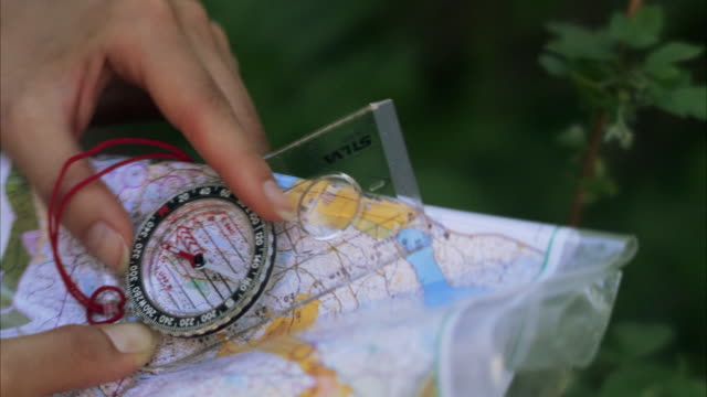 A hand a compass and a map Sweden.