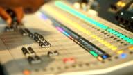 Hand adjusting audio mixer control panel.