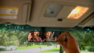 Hand adjusting car rear view mirror to reveal twin sisters waving in back seat
