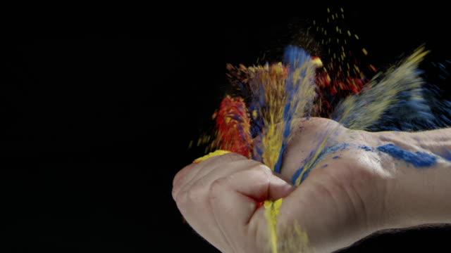 Hand black background caucasian human colorful powder holy slow motion