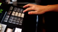 Hand entering amount on cash register in coffee shop.