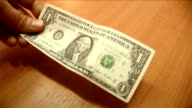 Hand gives dollar to another man