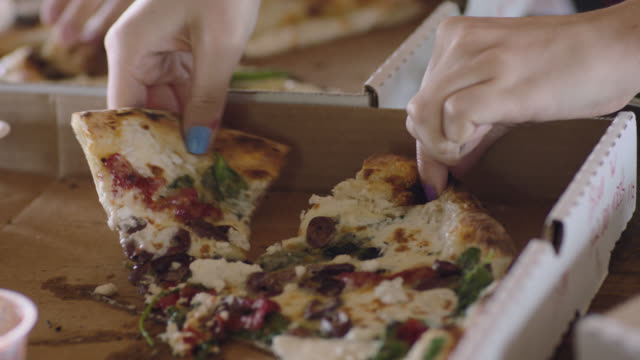 CU. Hand grabs a slice of gourmet pizza from a pizza box.