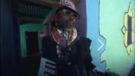 Hand held shot of a man in patterned hat and scarf playing an accordion in doorway of colourfully painted house Available in HD.