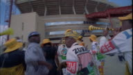 Hand held shot of Kaizer Chiefs fans in printed overalls dancing towards stadium entrance, Johannesburg Available in HD.