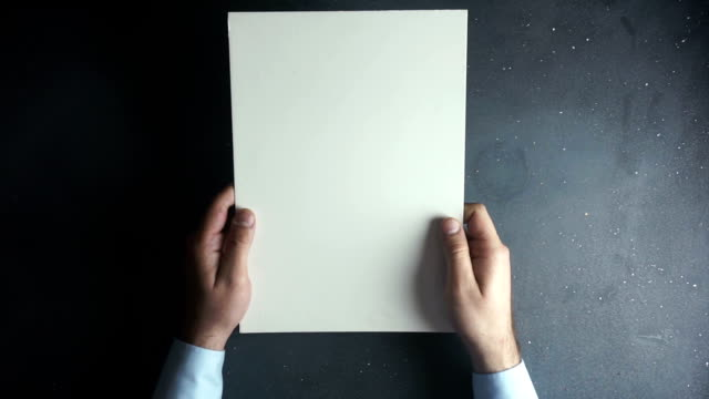 Hand holding blank brochure on black table