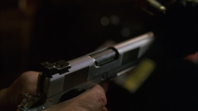 CU SLO MO Hand holding gun (9mm) and casing ejects while Firing